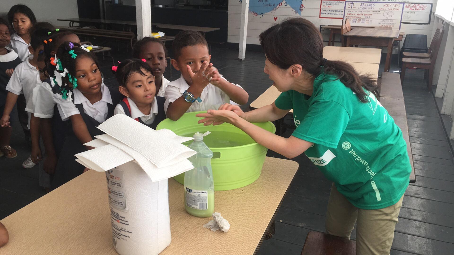 A intern demonstrates thorough handwashing during her Public Health internship in Belize for groups.